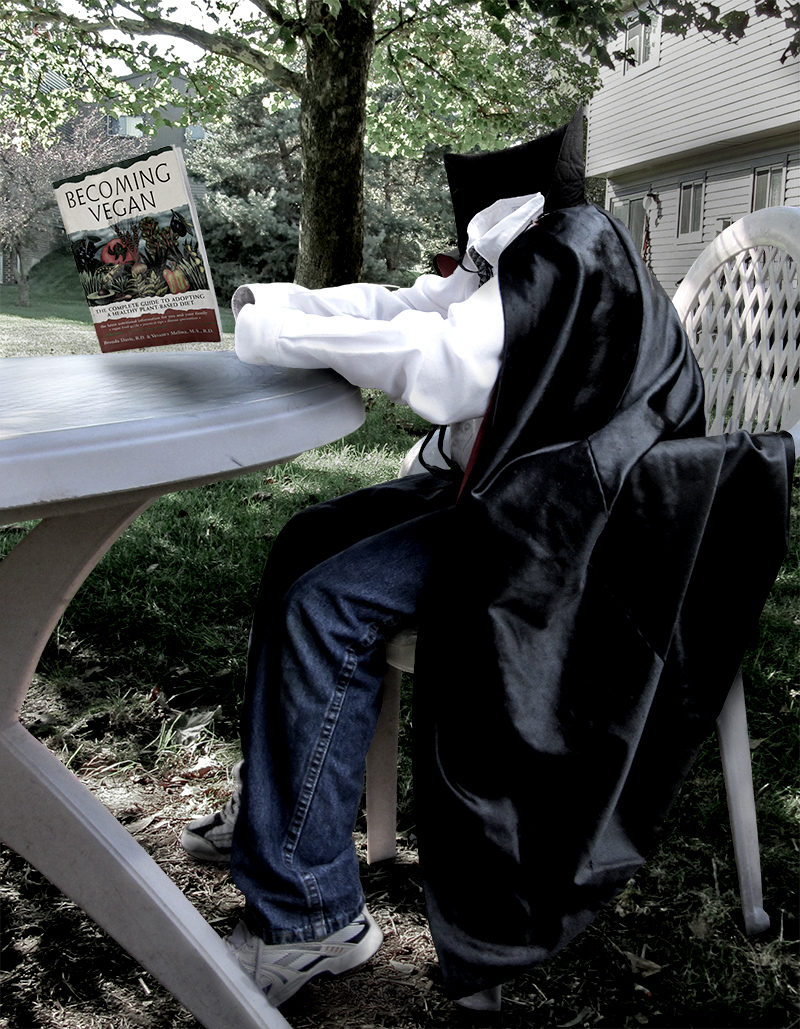 Invisible boy in a vampire cape, sitting at a table outside, reading a book about the vegan diet.